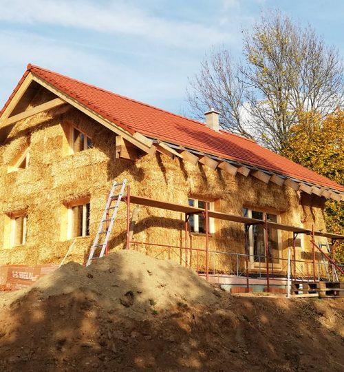 Nosná drevená konštrukcia domu po vyplnení slamenými balíkmi